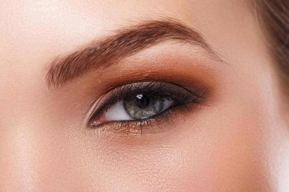 : Image of a woman's grey eye with complimenting eye shadow and a perfectly groomed eyebrow